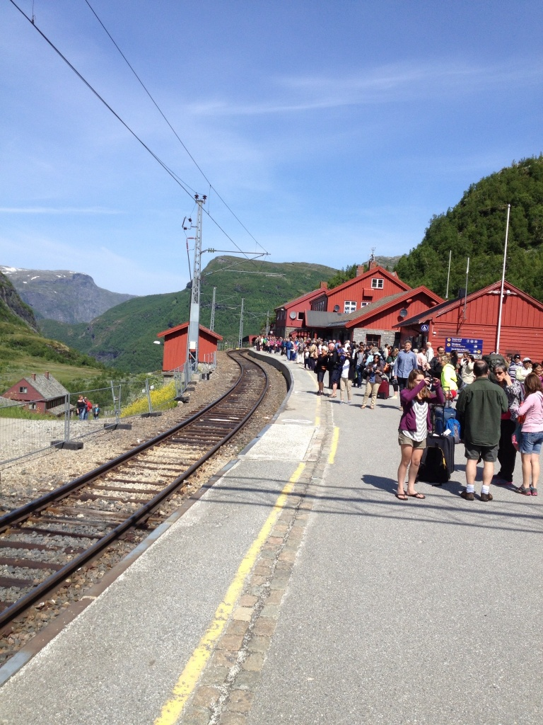 The cute train station and pile of tourists at the far end of the loading area.